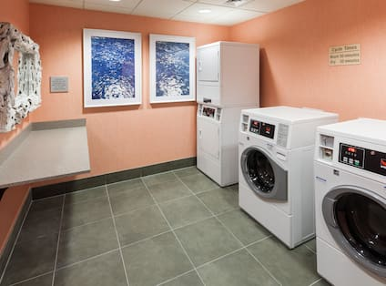 Laundry Room With Coin Operated Washers, Dryers, Folding Table, and Wall Art