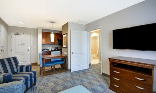Suite Living Room with Lounge Seating, Television, Kitchen and Entry to Bedroom