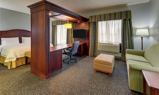 Suite with seating area, desk and bed