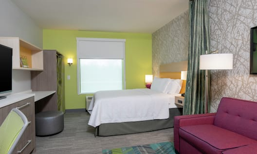 Bed in room with TV and couch