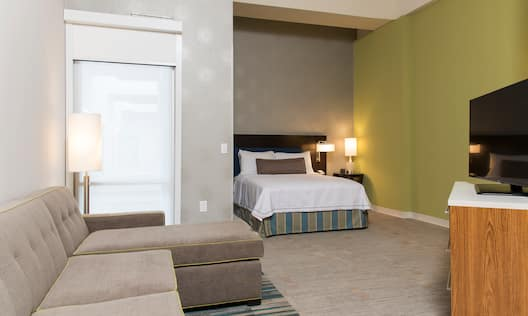 TV, Sofa, Floor Lamp by Window and Queen Bed With Lamp and Bedside Table  in Nook of Accessible Suite