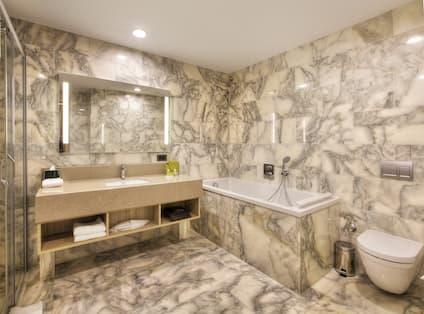 Junior Suite Bathroom With Vanity Mirror, Sink, Tub, and Toilet