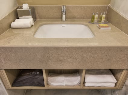 Bathroom Vanity and Sink With Fresh Towels, Toiletries, and Amenities