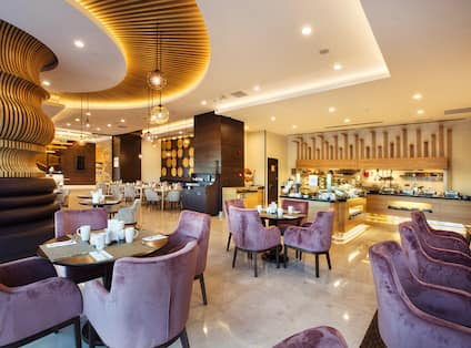Purple Chairs, Tables and Food Service Area in Lobby Bar