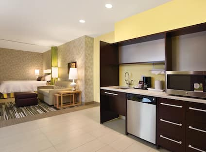 Kitchen With Dishwasher and Microwave, Living Area With Sofa, Lamps, Ottoman, and Green Partition Curtain Open to View of Queen Bed in Accessible Suite