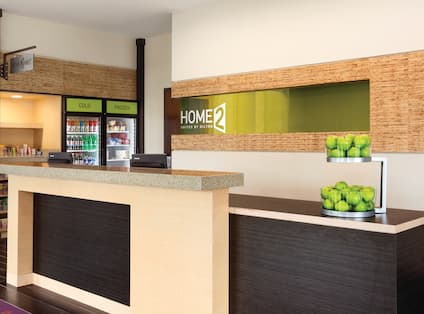 Green Apples on the Counter of Front Desk With Hotel Signage and Home2Market in the Background
