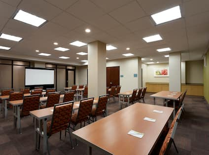 Classroom Style Meeting Room With Tables and Chairs Facing Presentation Screen