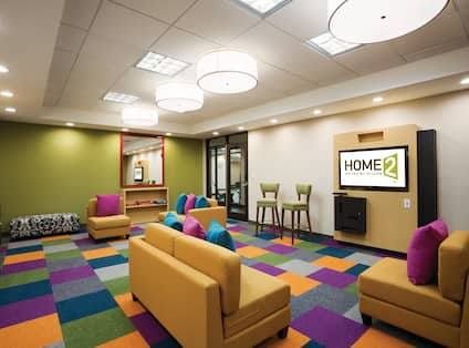 Media Room With Brightly Color Block Carpet, Soft Seating and Two TVs