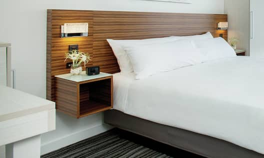 a king bed with a wall mounted headboard and nightstands