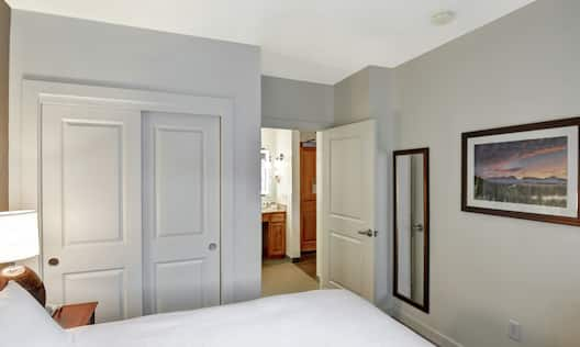 Guest Room with Bed, Closet, and Wall Art