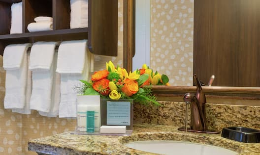 Close Up of Fresh Towels. Vanity Mirror, Sink, Flowers, and Toiletries