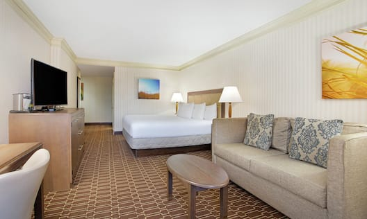 Corner King Guest Room with Sofa and Television