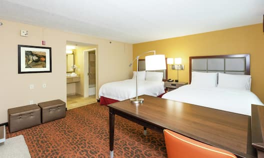 Guest Room With Illuminated Lamps Between Two Queen Beds, Work Desk, Sofa, and View into Bathroom