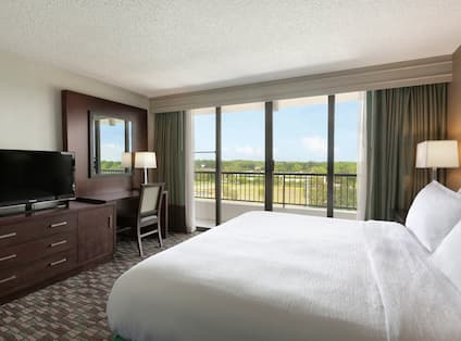 King Bed, TV, Work Desk, and Balcony Doors With Open Drapes in GUest Room