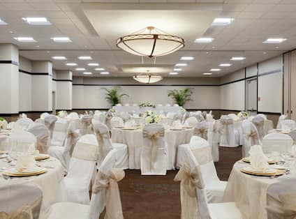 Round Tables With Flowers and Place Settings on White Linens in Ballroom Set Up for Wedding Reception