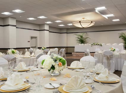 Close Up of Flowers, Place Settings, and White Linens on Round Tables Set for Wedding Reception