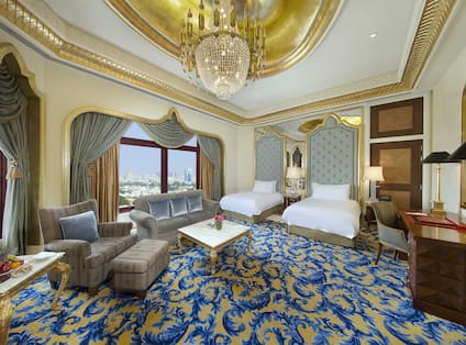 Qasr Room with two queen beds, lounge area, and outside view