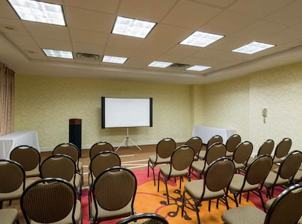 Meeting Room Arranged Theater Style With Rows of Chairs Facing Projector Screen