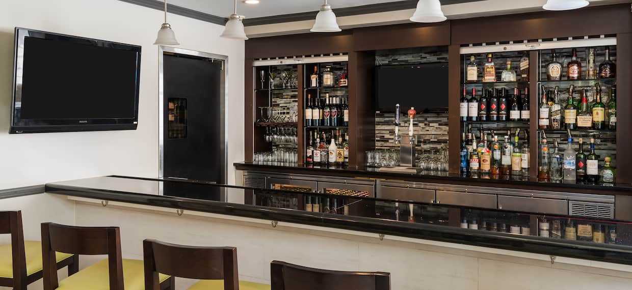 Fully Stocked Hotel Bar With Counter Seating and TV