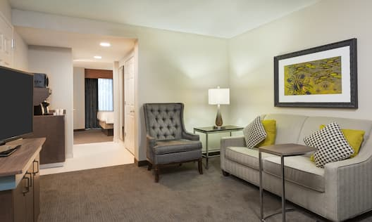 Junior Suite Living Room With Seating, Illuminated Lamp, TV, Hospitality Center, and View Into Bedroom