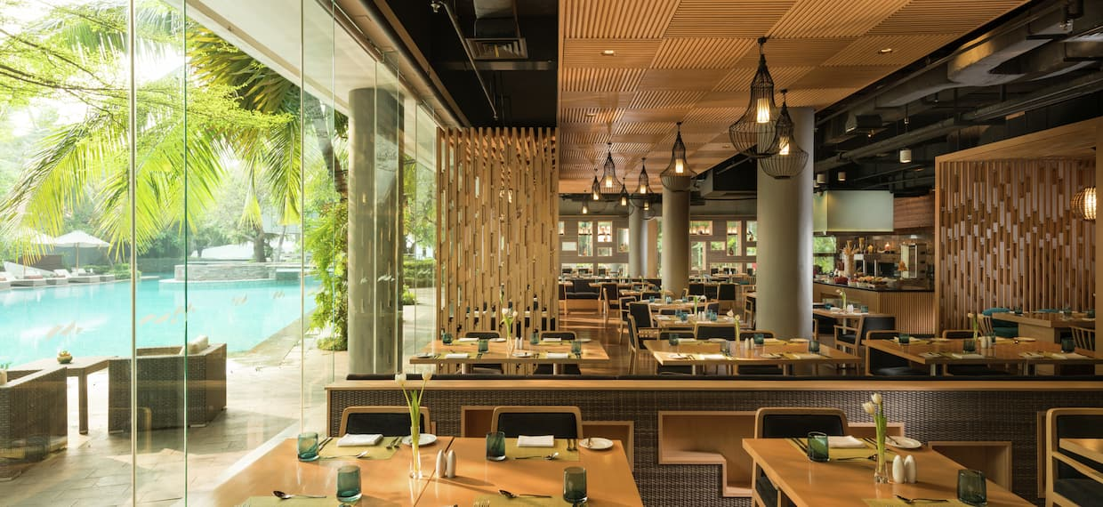 a restaurant dining room with a glass wall facing a swimming pool