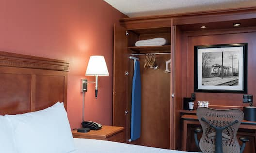 King Bed, Illuminated Lamp Over Bedside Table, Spacious Closet With Ironing Board, Blanket, and Hangers, and Work Desk in Guest Room