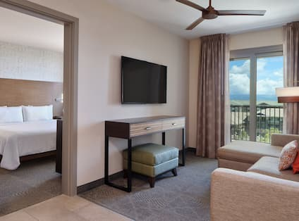 Suite Bedroom and Living Area with HDTV and Balcony View