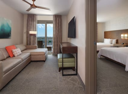 Suite Living Area with Balcony and View of Separate Bedroom with Two Beds