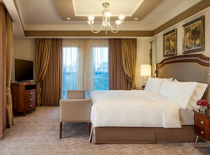 Suite Bedroom with Carpeting, Large Bed with Headboard, Bench, Bedside Tables, Lamps, Flat Screen TV, Framed Artwork, Mirrors, Tray Ceiling with Crown Molding and Recessed Lighting, Chandelier, and Large Windows with Curtains