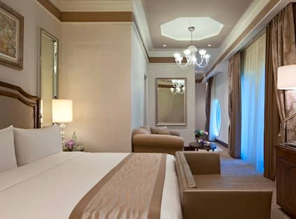 Suite with Large Bed, Bench, Sofa, Coffee Table, Lamps, Chandelier, and Large Window with Curtains