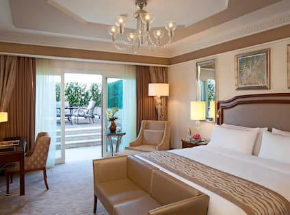 Room with Large Bed, Padded Headboard, Work Desk and Chair, End Table, Lamps, Framed Artwork, Tray Ceiling, Chandelier, Mirror, Sliding Door with Curtains, and Terrace with Outdoor Furniture