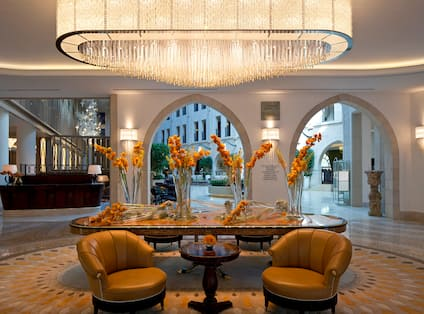 Entryway with Large Table and Flower Arrangements, Marble Flooring, Sconces, Sitting Area with Leather Armchairs and Cafe Table, Large Crystal Chandelier, and Archways Leading to Grand Atrium