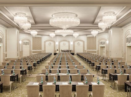 Ballroom with Tray Ceiling, Crystal Chandeliers, and Tables and Chairs Arranged in Classroom Layout