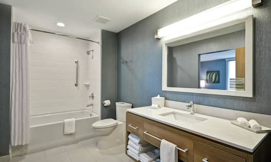 Vanity with Amenities and Bathtub and Shower Combo in Suite Bathroom