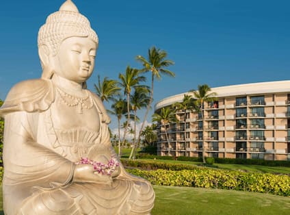 Buddha Statue with Hotel Exterior in Background