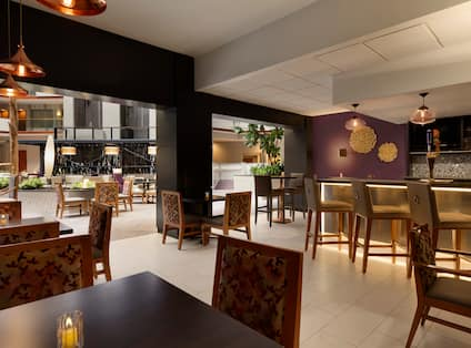 Bar with Stools, Beer Taps, Wine Bottles, Hightop Tables and Chairs, and View to Lobby Atrium