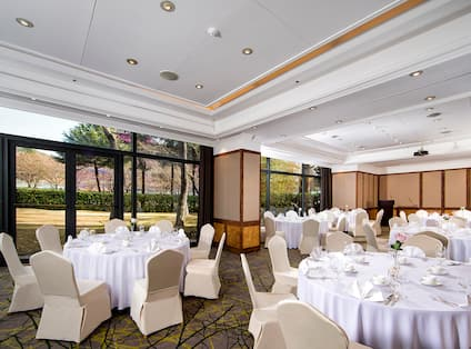 Spacious Ballroom Dining Area with Roundtables and Chairs