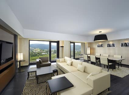 Guest Suite Lounge Area with Sofa, Coffee Table, Wall Mounted HDTV and Outside View