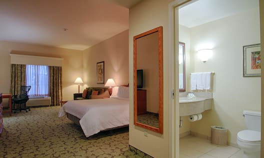 Work Desk by Window, Sofa, Bedside Table With Lamp, King Bed, Full Length Mirror, and Open Doorway to Bathroom With Brightly Lit Vanity Mirror, Sink, Fresh Towels, and Wall Art Above Toilet