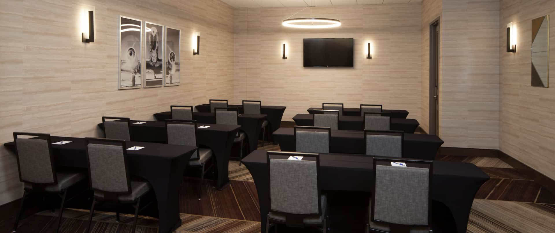 Meeting Room With Classroom Style Seating for 16 People, Wall Art, and TV in Front