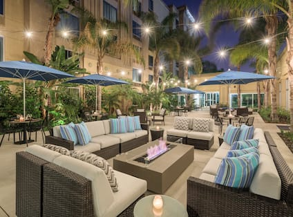 Exterior Courtyard seating area at night with dining tables, chairs, table umbrellas, lounge sofas, and palm trees