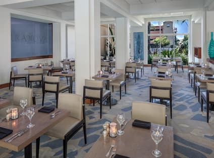 TerraNova Restaurant Dining Area with dining table, chairs, and floor-to-ceiling windows with an outdoor view