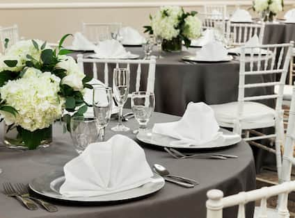 Ballroom with Round Tables and Chairs with Napkins on Plates