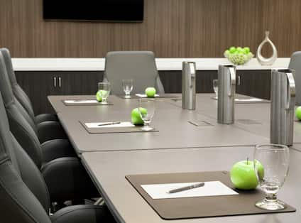 Boardroom with Tables, Chairs, Apples, and Glasses