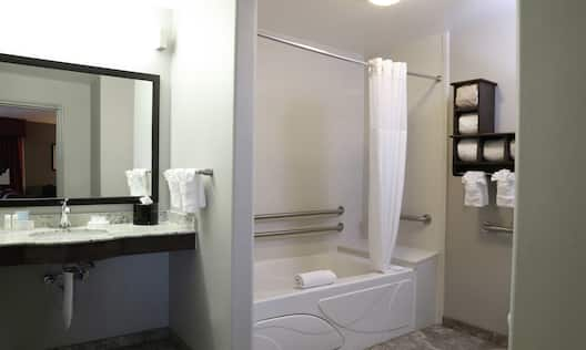 Accessible Guestroom Bathroom with Mirror, Vanity, Shower, and Bathtub