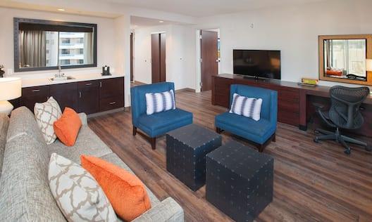 Living Area of 1 Bedroom Suite with Sofa, Chairs, Wet Bar, Open Doorway to Bedroom, TV, and Work Desk