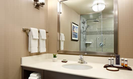 Luxury Bathroom With Fresh Towels, Wall Art and Shower With Glass Doors Reflected in Large Vanity Mirror, Sink, and Amenities