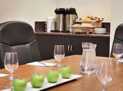 Close Up of Water and Apples on Boardroom Table