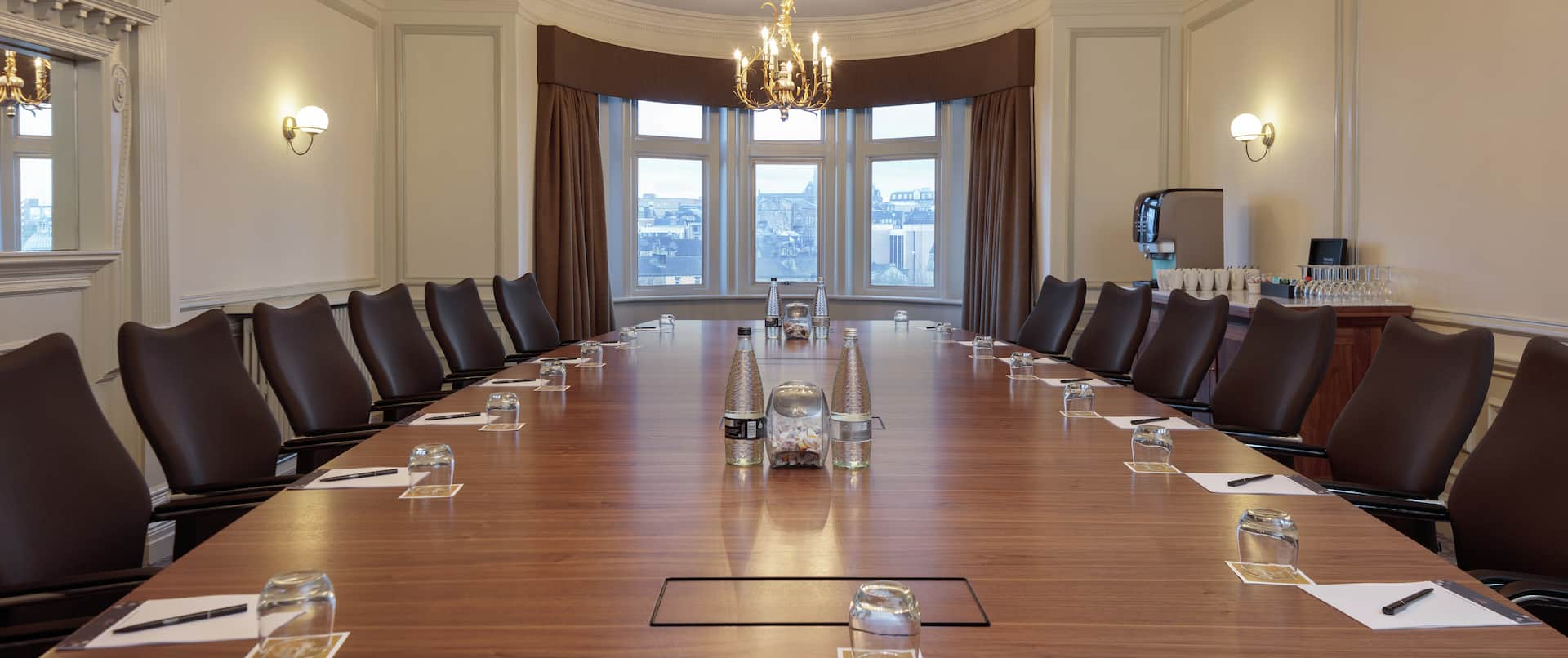 a large boardroom table with leather chairs in a private meeting room