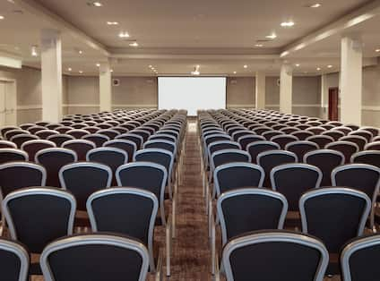 a large meeting room with presentation screen